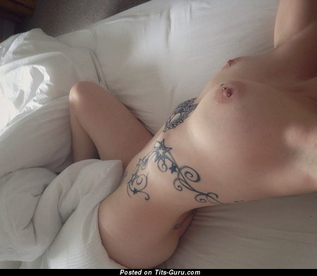 Image. Topless amateur beautiful lady with medium boobs, piercing and tattoo image