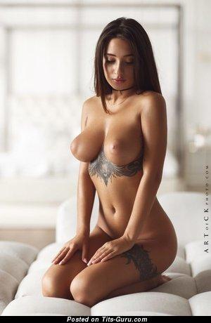 Фотография восхитительной брюнетки топлесс с среднего размера грудью, тату и большими сосками